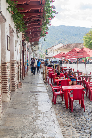 SANTA FE DE ANTIOQUIA, COLOMBIA - SEPTEMBER 3, 2015:  Restaurant tables on Plaza Mayor Simon Bolivar square in Santa Fe de Antioquia, Colombia.