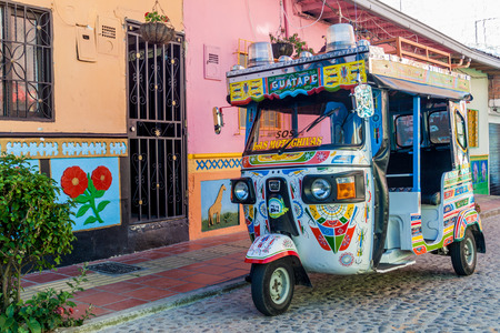 mototaxi: GUATAPE, COLOMBIA - SEPTEMBER 2, 2015: Colorful mototaxi (tuk tuk) and decorated houses in Guatape village, Colombia Editorial