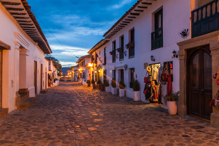 Evening moody view of a cobbled street in colonial town Villa de Leyva, Colombia. Banco de Imagens