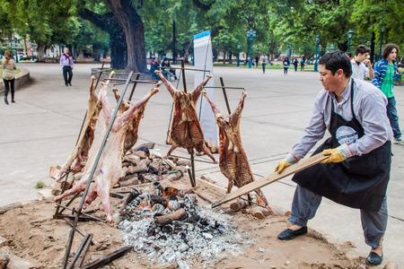 MENDOZA, ARGENTINA - MARZO 30 de, 2015: asado tradicional - barbacoa de un cordero. Plaza Independencia en Mendoza, Argentina. Foto de archivo - 60903895