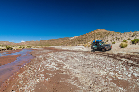 SOUTHWESTERN BOLIVIA - APRIL 14, 2015: 4WD vehicle carries group of tourists at the popular Salar de Uyuni tour. Editorial