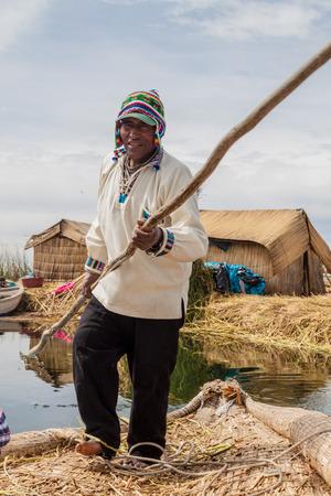 navigable: TITICACA, PERU - MAY 15, 2015: Boatman, inhabitant of Uros floating islands, Titicaca lake, Peru Editorial