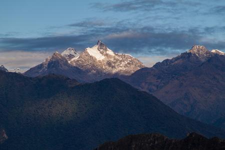 Sun is rising over snow capped mountain near Machu Picchu ruins, Peru