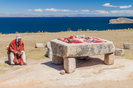 sacrifices: ISLA DEL SOL, BOLIVIA - MAY 12, 2015: Native man in traditional clothing next to the Ceremonial table used to be probably place of human sacrifices at Isla del Sol (Island of the Sun) in Titicaca lake, Bolivia Editorial