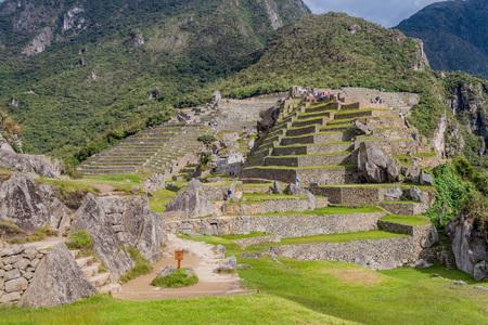 high priest: MACHU PICCHU, PERU - MAY 18, 2015: Crowds of visitors in House of the High Priest at Machu Picchu ruins, Peru. Editorial