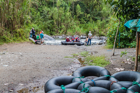 tubing: MINDO, ECUADOR - JUNE 27, 2015: Group of tourists is preparing for tubing.