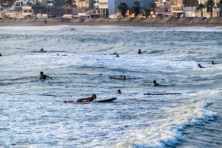 HUANCHACO, PERU - JUNE 6, 2015: People surf in waves of an ocean in Huanchaco, Peru. Editorial