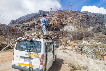 guides: PASO ZONGO, BOLIVIA - APRIL 25, 2015: Mountain guides unload wood carried to mountain refuge Huayna Potosi Refugio, in the altitude of 4700m.