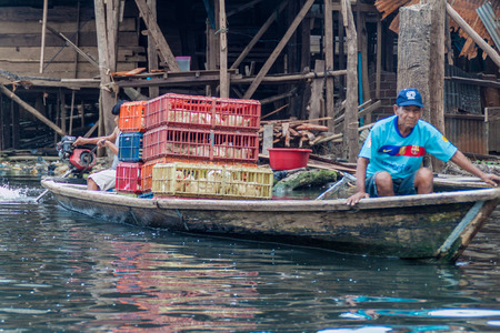 shantytown: IQUITOS, PERU - JULY 18, 2015: Boatmen in partially floating shantytown in Belen neigbohood of Iquitos, Peru. Editorial