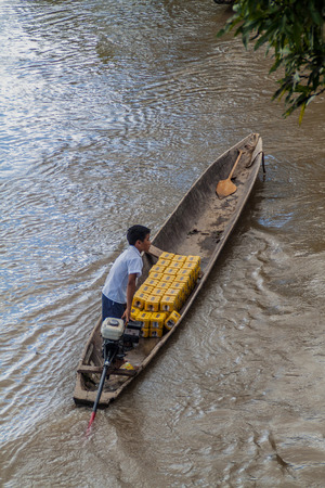 villager: NAPO, PERU - JULY 15, 2015: Villager transports beer cans in a canoe on a river Napo, Peru Editorial
