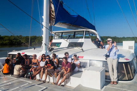 salut: KOUROU, FRENCH GUIANA - AUGUST 2, 2015: Tourists aboard modern catamaran on their way to Iles du Salut (Islands of Salvation) in French Guiana. Editorial