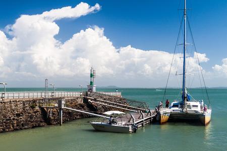 salut: ILE ROYALE, FRENCH GUIANA - AUGUST 2, 2015:  Modern catamaran anchored by Ile Royale, one of the islands of Iles du Salut (Islands of Salvation) in French Guiana.