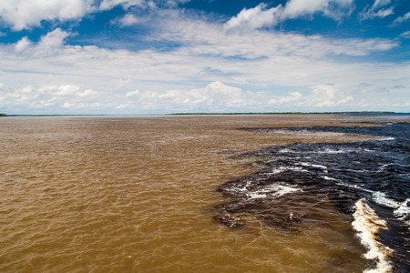 rio amazonas: The Meeting of Waters (Encontro das Aguas) is the confluence between the Rio Negro river, with dark water, and lighter Amazon river or Rio Solimoes Foto de archivo