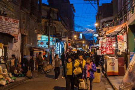 LA PAZ, BOLIVIA - APRIL 23, 2015:  People walk on a night stret in the center of La Paz, Bolivia.