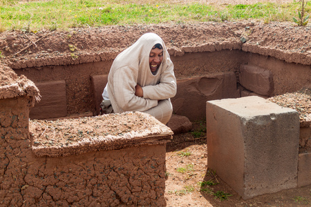 tourist guide: TIWANAKU, BOLIVIA - APRIL 24, 2015: Tourist guide shows the position of bodies in a grave,Tiwanaku ruins, Titicaca region, Bolivia. Editorial