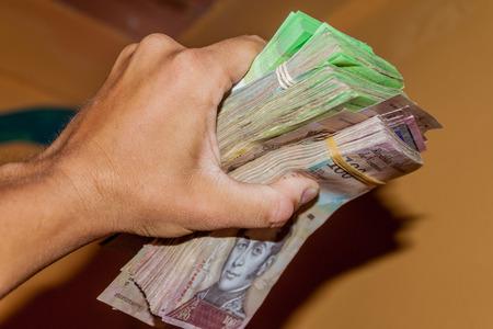 Pila de la moneda venezolana (Bolívar Fuerte) es sostenido en la mano. Debido a la hiperinflación, es necesario el uso de grueso fajo de billetes para cubrir las necesidades básicas. Foto de archivo