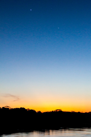 jupiter light: View of a sunset over Amazon river in Brazil. Planets Venus and Jupiter are also visible.