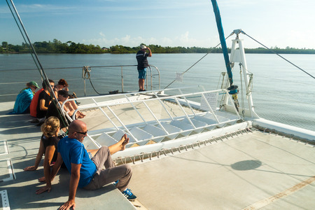 the french way: KOUROU, FRENCH GUIANA - AUGUST 2, 2015: Tourists aboard modern catamaran on their way to Iles du Salut (Islands of Salvation) in French Guiana. Stock Photo
