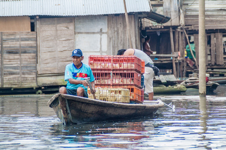 shantytown: IQUITOS, PERU - JULY 18, 2015: Boatmen in partially floating shantytown in Belen neigbohood of Iquitos, Peru. Stock Photo