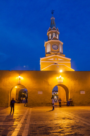 walled: CARTAGENA DE INDIAS, COLOMBIA - AUG 27, 2015: People walk at the Plaza de los Coches in Cartagena during evening. Clock tower in the background.