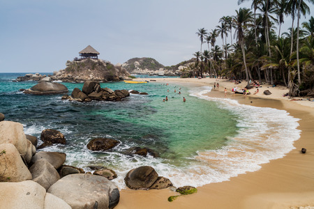 TAYRONA, COLOMBIA - AUGUST 26, 2015: People enjoy beautiful waters of Carribean sea in Tayrona National Park, Colombia