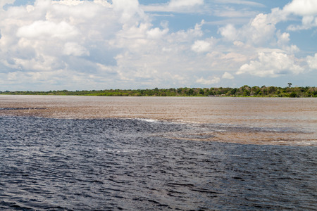 waters: The Meeting of Waters (Encontro das Aguas) is the confluence between the Rio Negro river, with dark water, and lighter Amazon river or Rio Solimoes Stock Photo