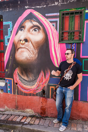 guia turistico: BOGOTA, COLOMBIA - SEPTEMBER 24, 2015: Graffiti tour guide stays at the wall covered by graffiti in the La Candelaria neighborhood of Bogota, capital of Colombia.