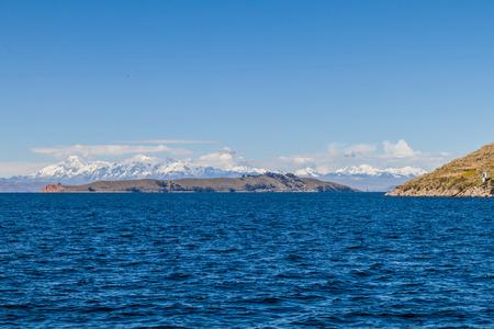 Cordillera Real mountain range behind Titicaca lake, Bolivia. Isla de la Luna also visible. Stock Photo