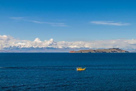 Cordillera Real mountain range behind Titicaca lake, Bolivia. Isla de la Luna and a traditional boat also visible. Stock Photo