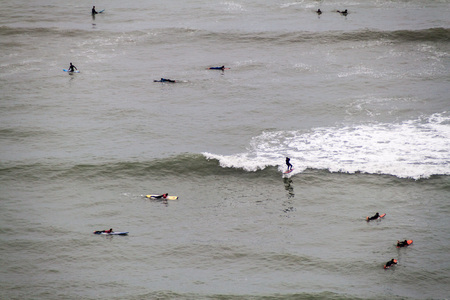 lima: LIMA, PERU - JUNE 4, 2015: People surf on waves of an ocean. Miraflores district of Lima, Peru.