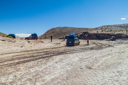 SOUTHWESTERN BOLIVIA - APRIL 14, 2015: 4WD vehicles carry group of tourists at the popular Salar de Uyuni tour.