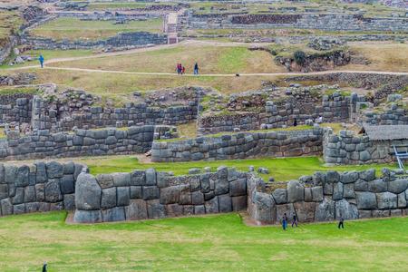 SACSAYWAMAN, PERU - MAY 24, 2015: Tourists visit  Incas ruins of Sacsaywaman near Cuzco, Peru.