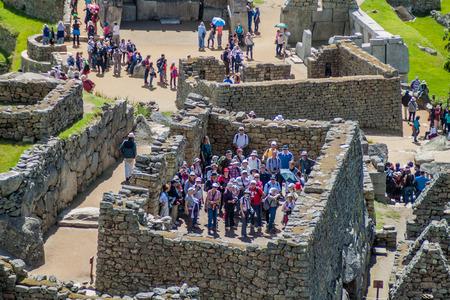 high priest: MACHU PICCHU, PERU - MAY 18, 2015: Crowds of visitors in House of the High Priest at Machu Picchu ruins, Peru. Stock Photo