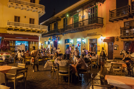 CARTAGENA DE INDIAS, COLOMBIA - AUG 27, 2015: People sit in cafes at Plaza Fernandez de Madrid square in Cartagena during the evening.