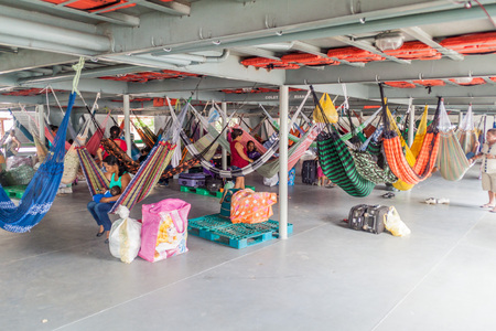 plies: TABATINGA, BRAZIL - JUNE 22, 2015: Passengers of hammock deck at the boat Diamante which plies river Amazon between Tabatinga and Manaus, Brazil.