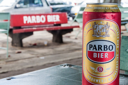 PARAMARIBO, SURINAME - AUGUST 6, 2015: Can of Parbo beer, product of Surinamese Brewery,  subsidiary of Heineken. Parbo advertisement on a bench, out of focus.