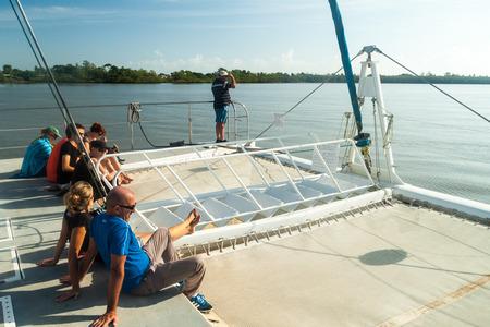 salut: KOUROU, FRENCH GUIANA - AUGUST 2, 2015: Tourists aboard modern catamaran on their way to Iles du Salut (Islands of Salvation) in French Guiana. Stock Photo