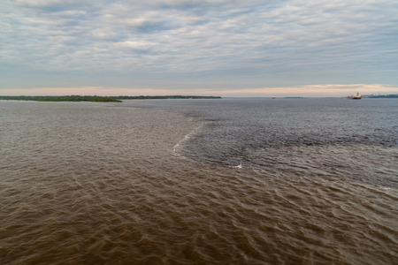 The Meeting of Waters (Encontro das Aguas) is the confluence between the Rio Negro river, with dark water, and lighter Amazon river or Rio Solimoes Reklamní fotografie