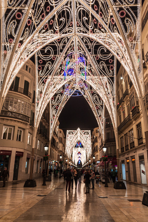 MALAGA, SPAIN - JAN 25, 2015: People walk through decorated pedestrianized Calle Larios in Malaga.