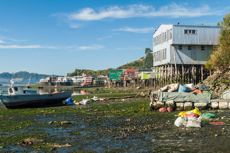 CASTRO, CHILE - MARCH 23, 2015: Fishing boats and palafitos (stilt houses) during low tide in Castro, Chiloe island, Chile
