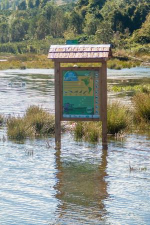 CURACO DE VELEZ, CHILE - MARCH 21, 2015: Partially submerged tourist information board in Curaco de Velez village, Quinchao island, Chile Editorial