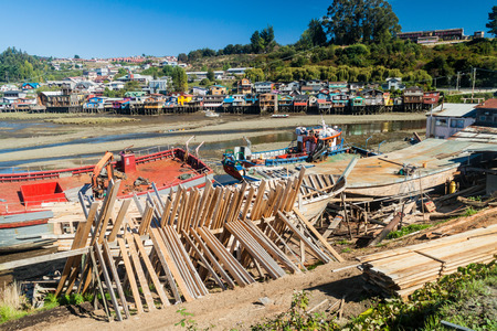 Fishing boats and palafitos (stilt houses) during low tide in Castro, Chiloe island, Chile