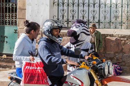 SUCRE, BOLIVIA - 22 APRILE 2015: La guardia del traffico della zebra sta aiutando con il traffico a Sucre, capitale della Bolivia Archivio Fotografico - 78726426