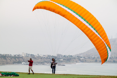 LIMA, PERU - JUNE 4, 2015: Paraglider gets ready to fly over cliffs of Miraflores district of Lima