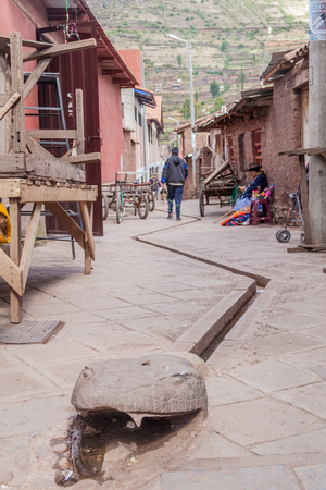 PISAC, PERU - MAY 22, 2015: Serpent styled sewer in Pisac, Sacred Valley of Incas, Peru.