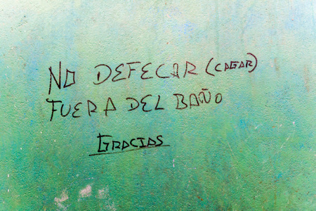 Hand written text on a rural peruvian toilet says: Do not defecate outside of the toilet. Thank you. Stock Photo