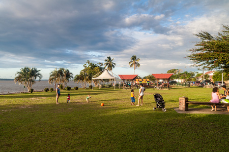 ST LAURENT DU MARONI, FRENCH GUIANA - AUGUST 4, 2015: People on a riverbank park in St Laurent du Maroni, French Guiana.