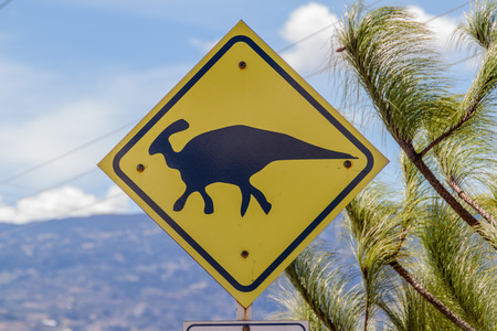 Dinosaur warning sign near Villa de Leyva in Colombia. This area is famous for numerous findings of fossils. Stock Photo