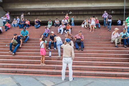 eponymous: MEDELLIN, COLOMBIA - SEPTEMBER 1, 2015: People sit on the stair between Parque Berrio and eponymous metro station in Medellin