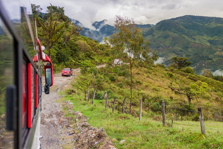 Bus is riding on a muddy road in Cuenca region of Colombia